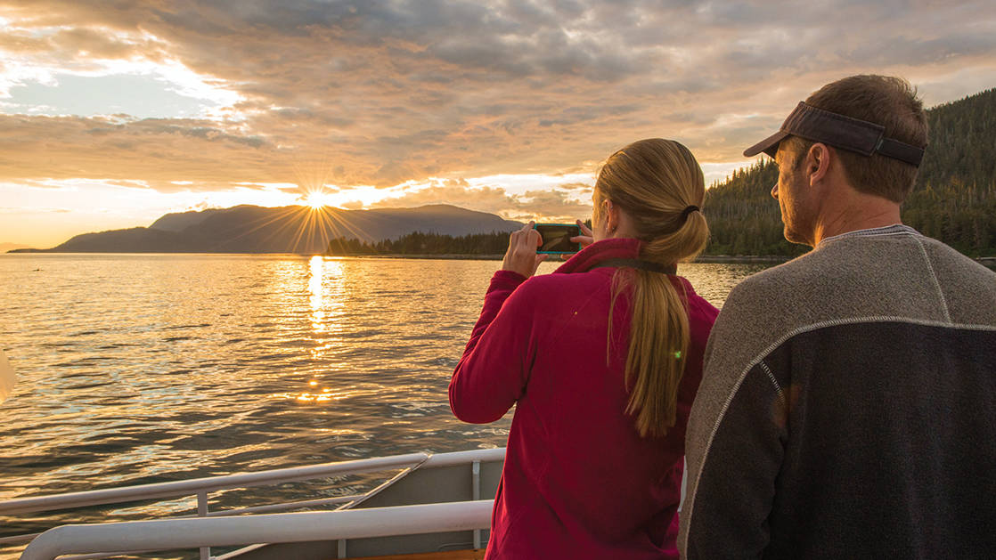 small ship guests aboard National Geographic Sea Bird looking at the sunset on the Exploring British Columbia & the San Juan Islands cruise