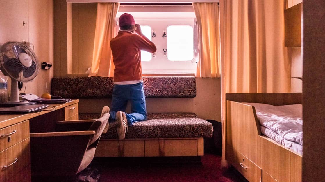 50 Years of Victory: Poseidon with a passenger viewing out the window of a twin berth stateroom with bench seating, desk and chair.