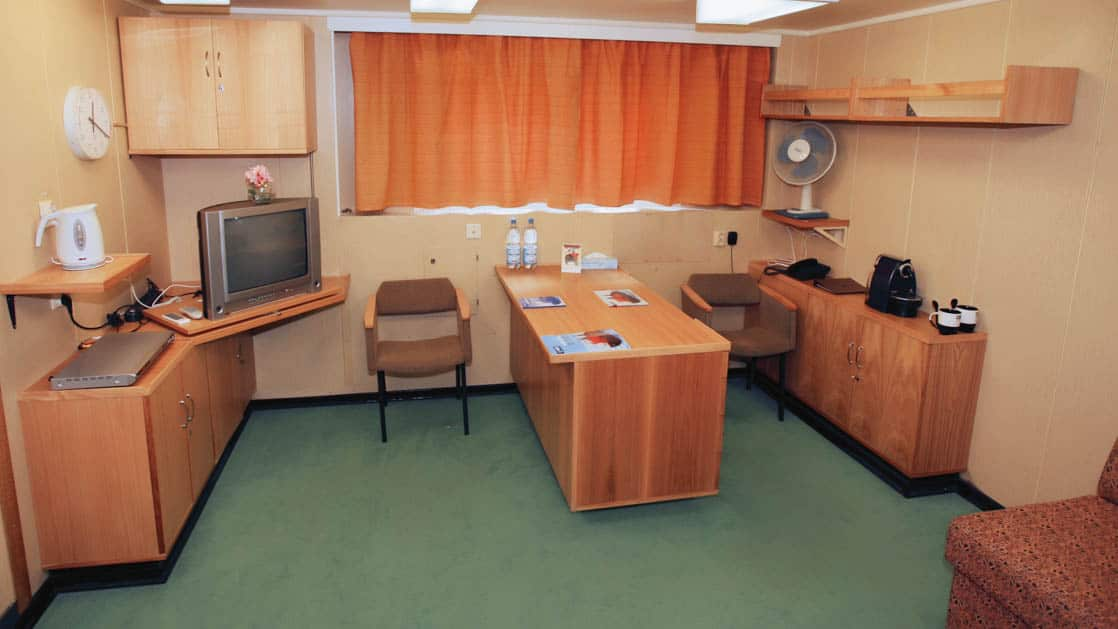 50 Years of Victory: Poseidon junior suite with desk, cabinet space, windows, TV and seating.