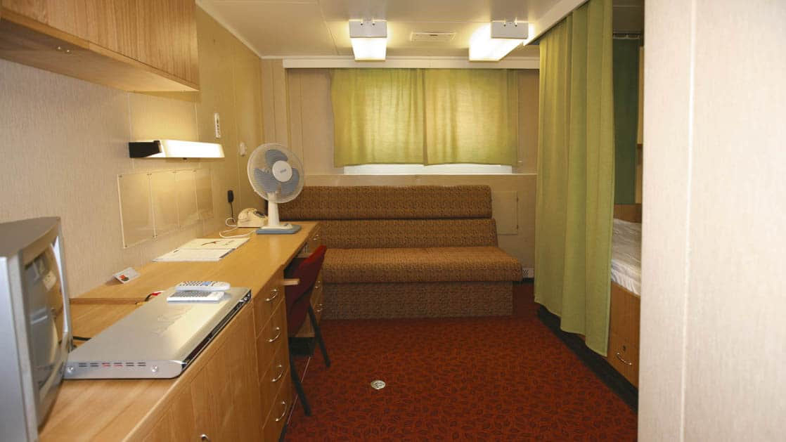 50 Years of Victory: Poseidon twin berth with bench seating, desk, TV, fan and windows.