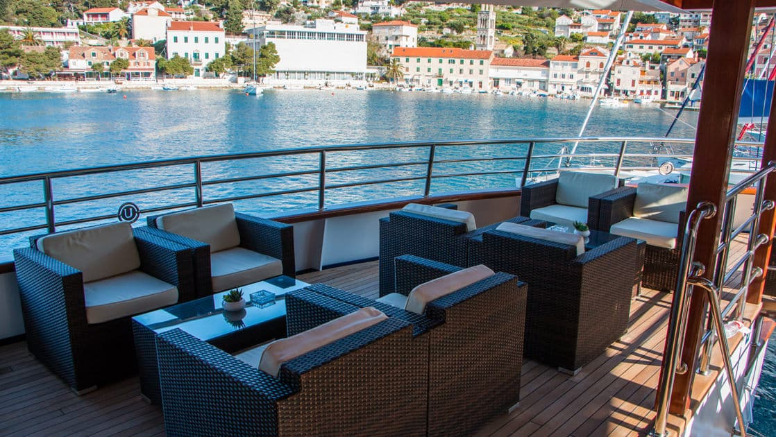 Small ship cruise Futura outdoor deck on the stern with couches, chairs and coffee table.