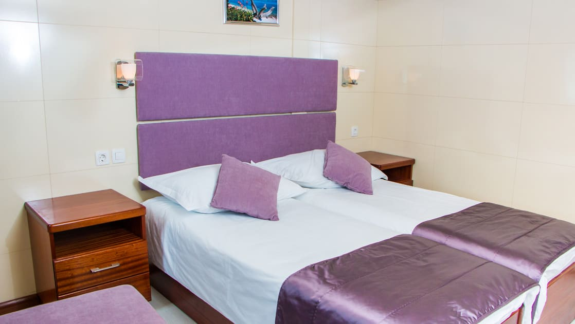 Small ship cruise Futura lower deck cabin with double bed, nightstands, night lights and seat.
