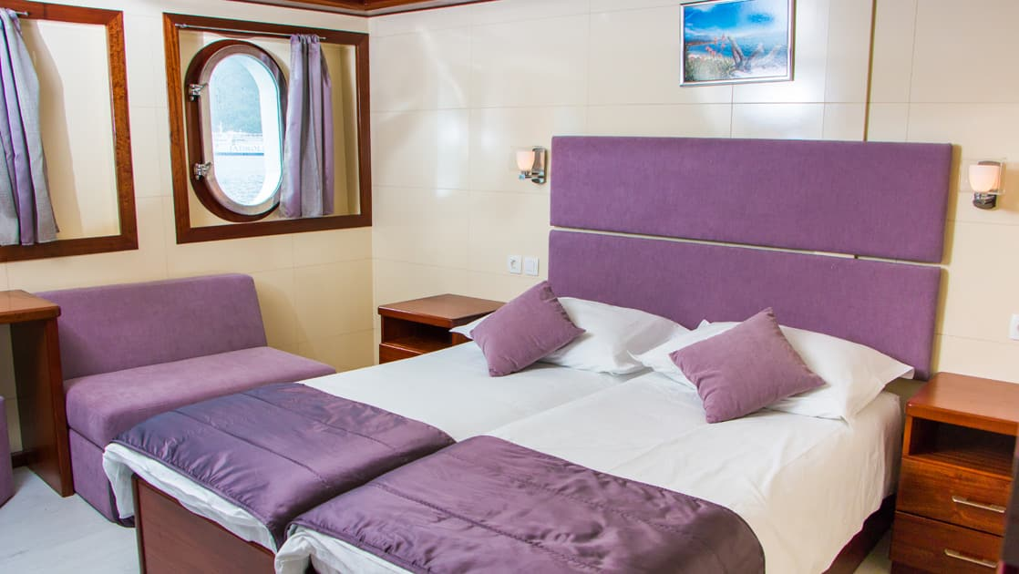 Small ship cruise Futura main deck cabin with double bed, 2 windows, seating area, nightstand, and night lights.