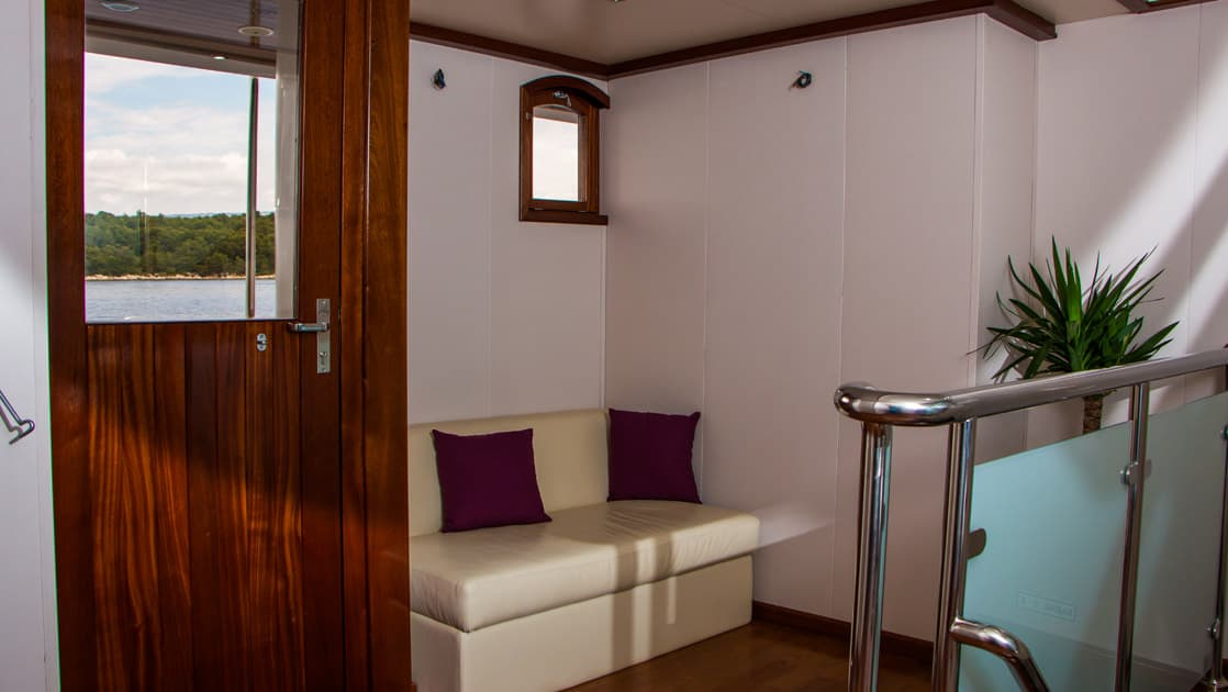 Small ship cruise Futura hallway with bench seating and door access to the outside balcony.