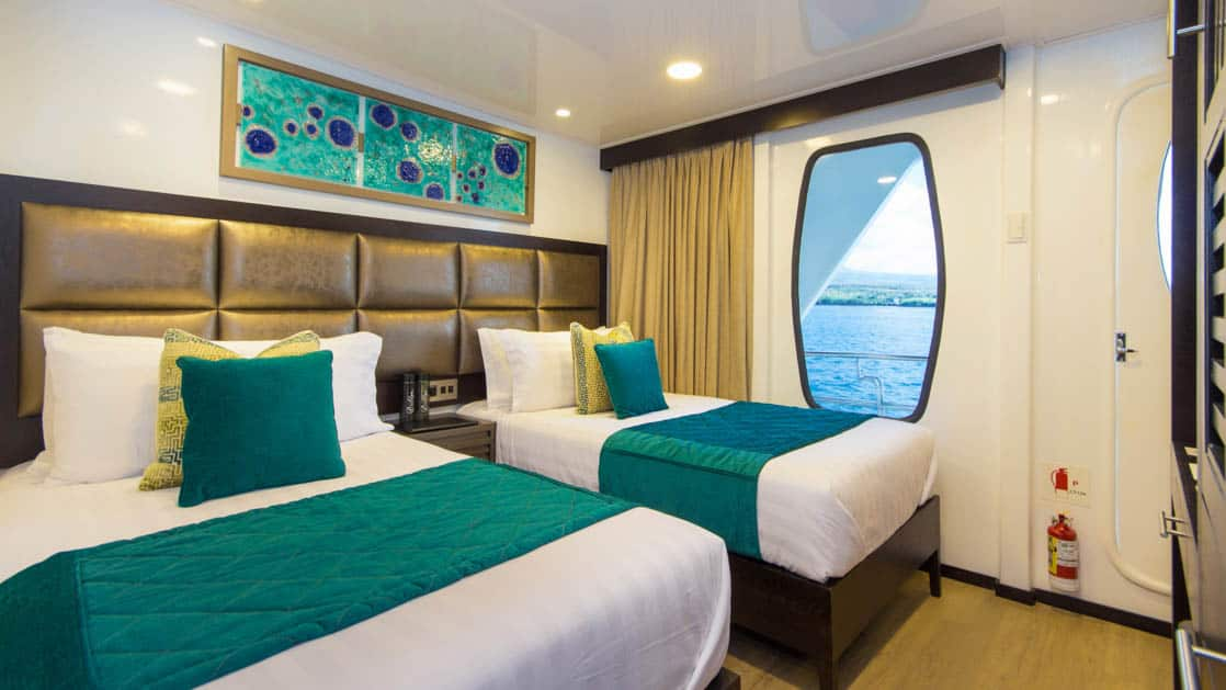 Twin Cabin aboard Alya with two single beds, window, and entry door.