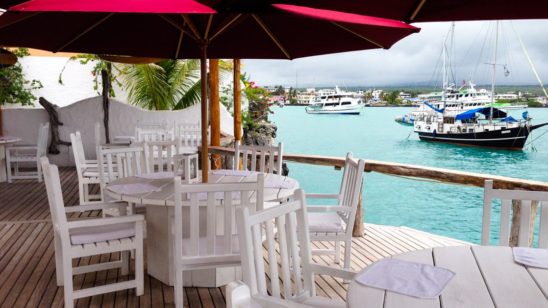 White tables and chairs on the outdoor patio overlooking bright blue teal waters of the harbor in the Galapagos
