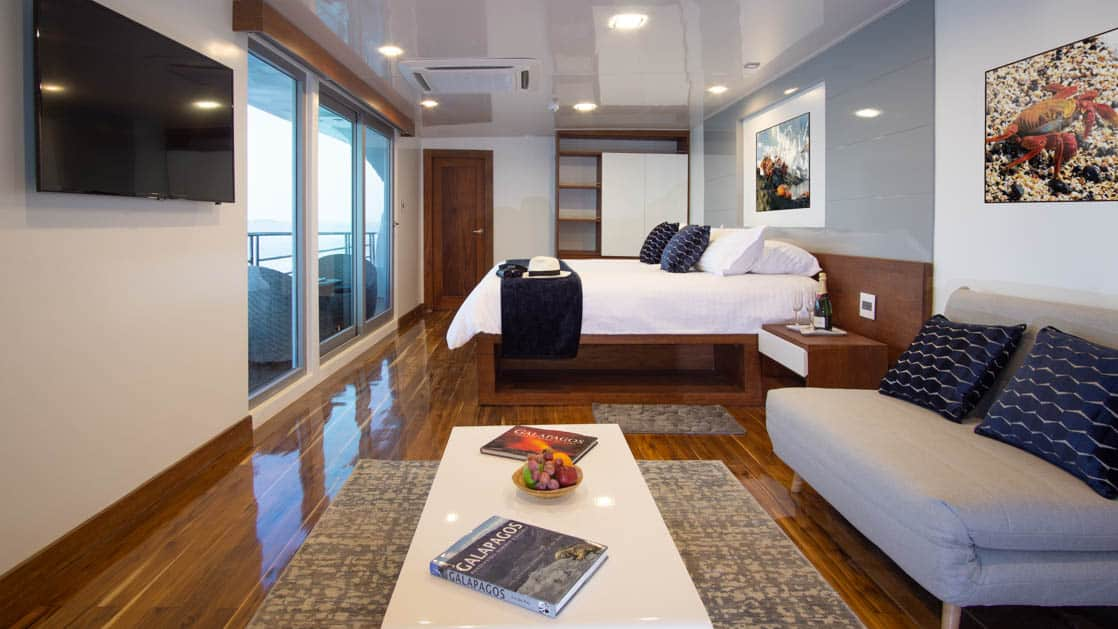 Galapagos Infinity yacht suite with couch, coffee table, king size bed floor to ceiling windows and balcony.