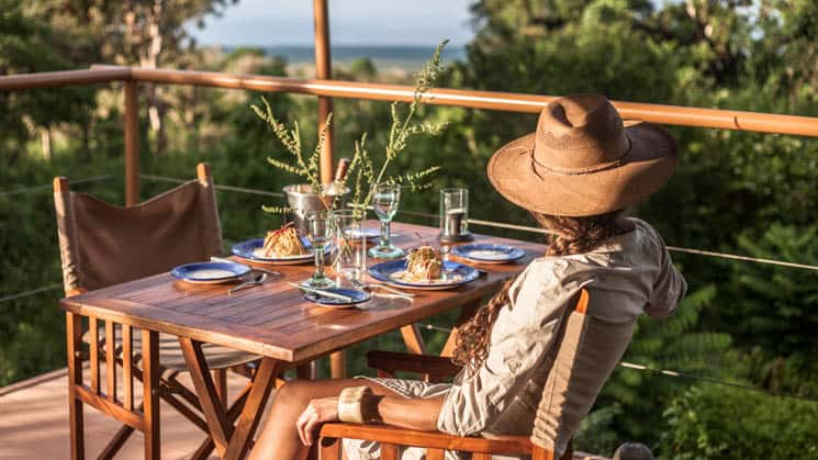 Woman with wide-brim hat sitting at table on outside deck with forest and ocean views at Galapagos Safari Camp Santa Cruz Highlands in the Galapagos Islands