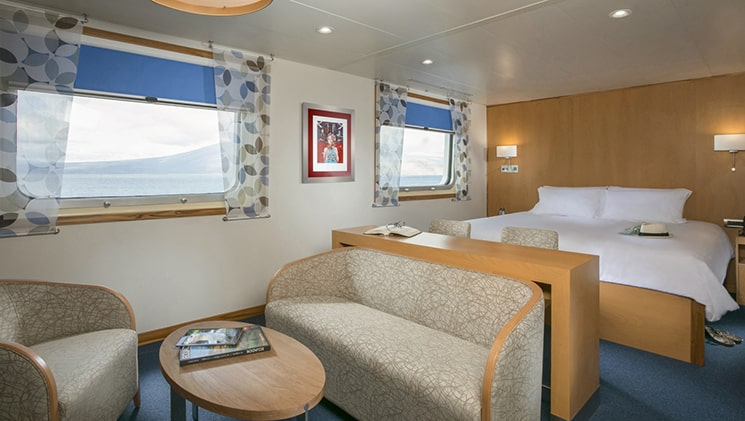 a double bed cabin with a large bed, couch, table and chairs and 2 large windows aboard the Santa Cruz II Galapagos small ship