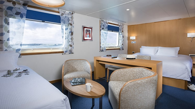 suite aboard the Santa Cruz II Galapagos small ship with 2 beds, a table and chairs and 2 large windows