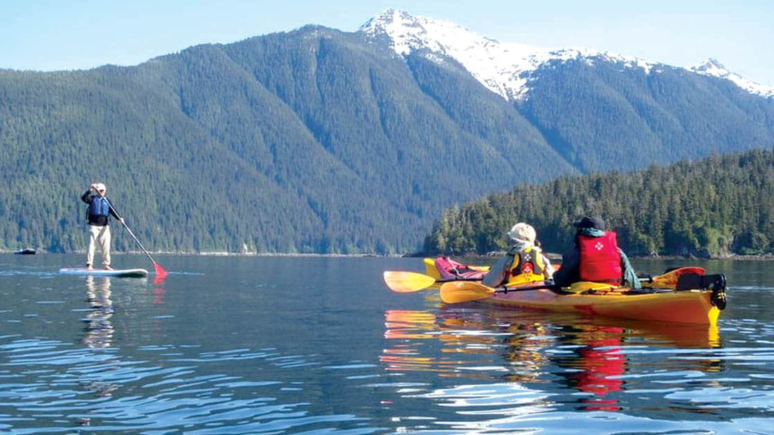 travelers kayaking and stand up paddleboarding during the glacier bay national park adventure cruise trip