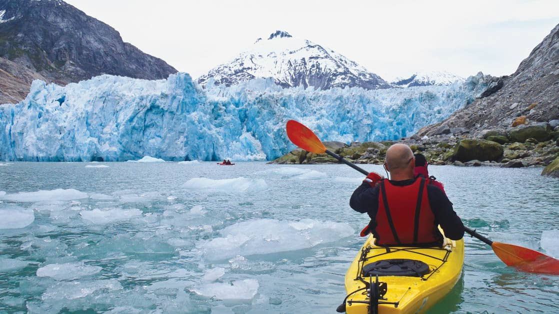 man kayaking in alaska with a glacier in front of him
