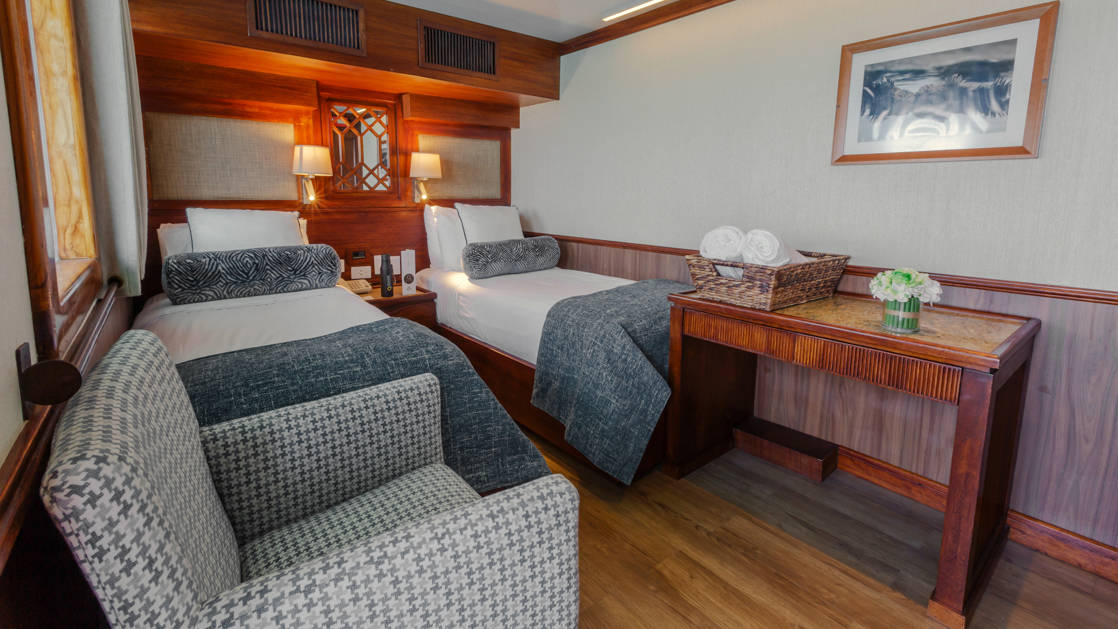 Grace stateroom with twin beds, seating area, desk and nightstand.