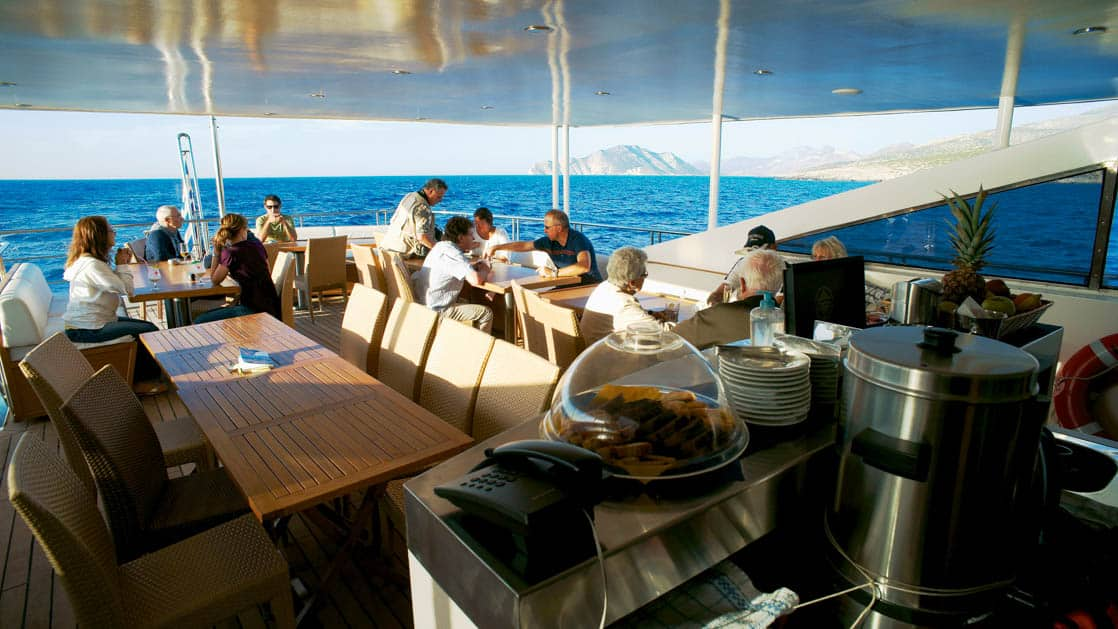Harmony G yacht outdoor deck dining with large tables, chairs and coffee and snack service station.