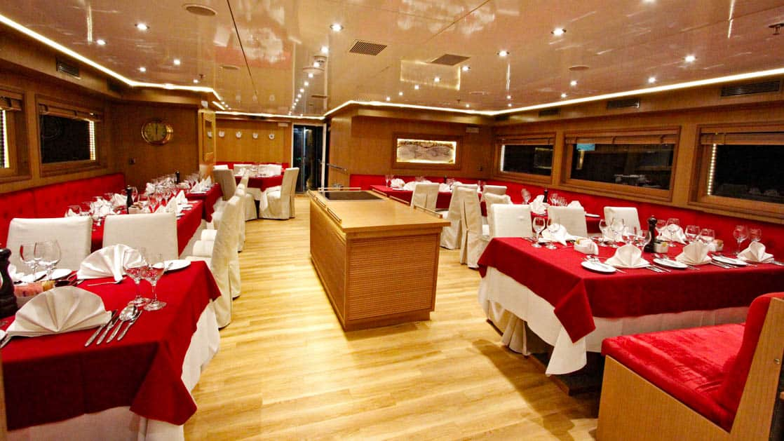 Harmony G yacht dining room with tables and chairs set up for a meal and windows.
