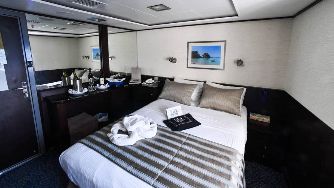 Harmony V Category C stateroom with double bed, 2 small windows and bathroom.