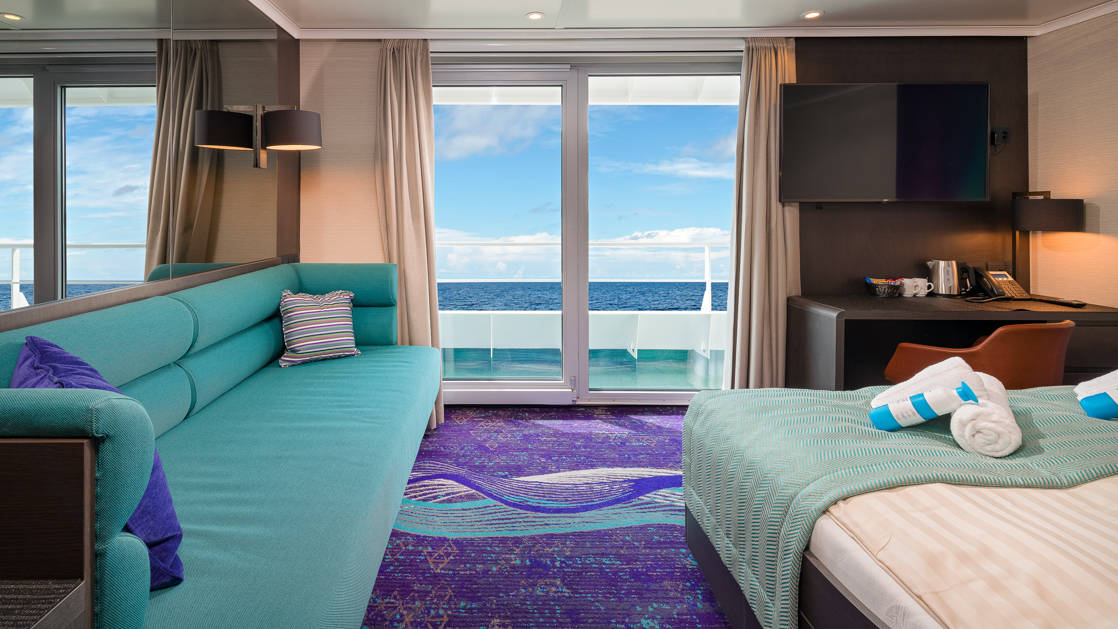 Grand Suite aboard Hondius and Janssonius polar small ships, with teal and purple accents, couch, double bed & balcony.