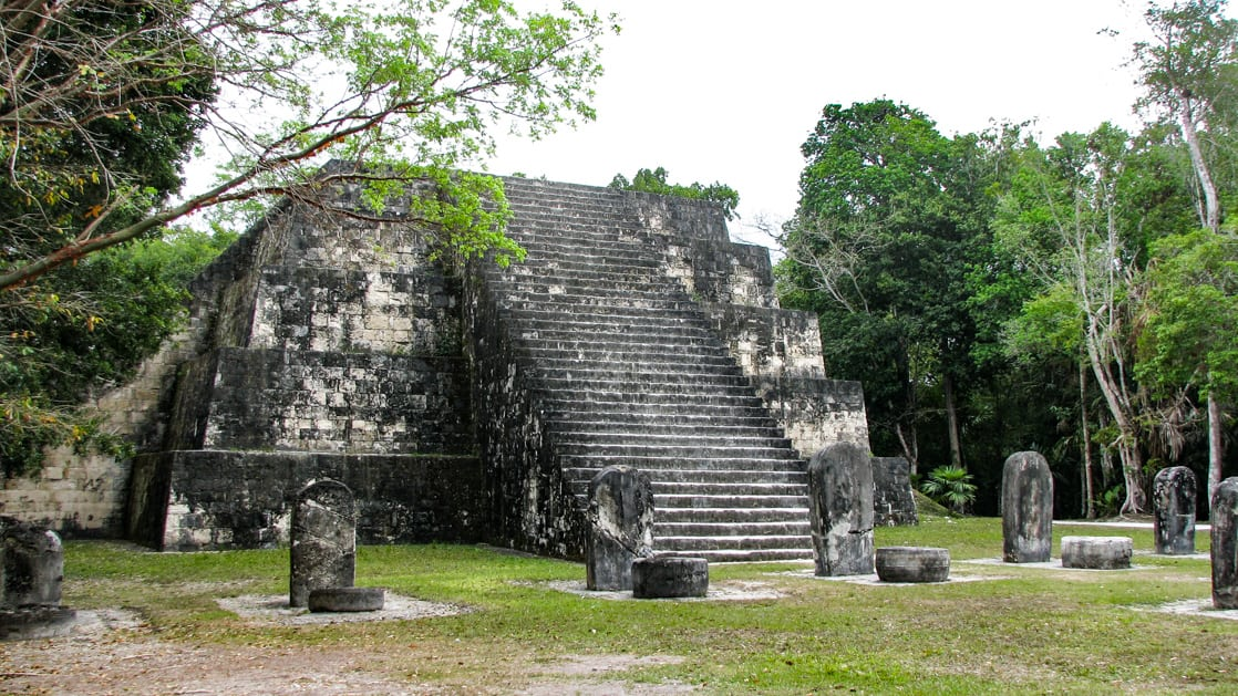 A pyramid in Tikal with many steps to a flat platform.