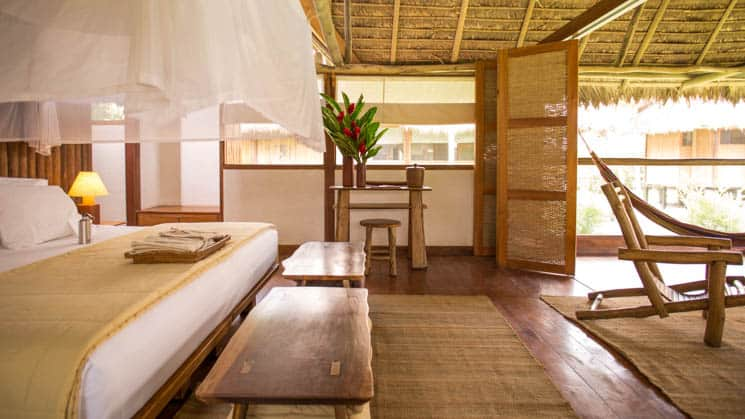 A bed with linens, wood furniture, open windows, and a mosquito net are inside the Amazonica Suite, a rustic comfort option at Inkaterra Reserva Amazonica