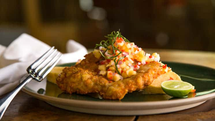 Fish is served on a plate with a mango salsa and a lime at the restaurant at Inkaterra Reserva Amazonica. Meals and beverages prepared with fresh local ingredients.