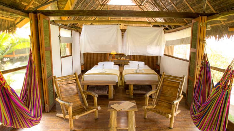 The Superior Rio room with two beds and two rocking chairs at Inkaterra Reserva Amazonica provides rustic comfort in Peru's Amazon rainforest.