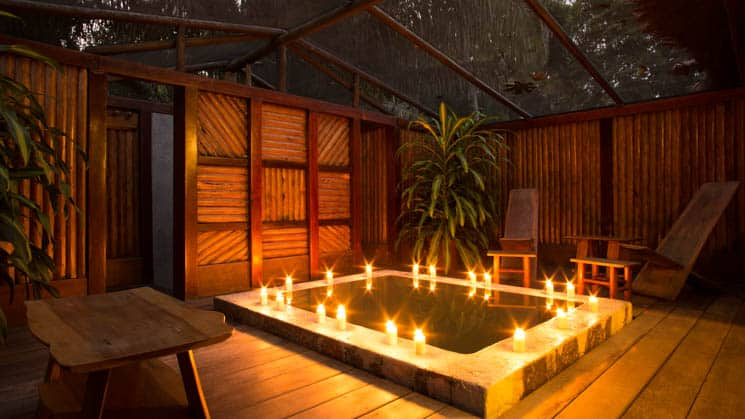 Candles are lit around the permitter of a jacuzzi at the Tambopata Suite, in a private covered terrace, at the Inkaterra Reserva Amazonica hotel in Peru.