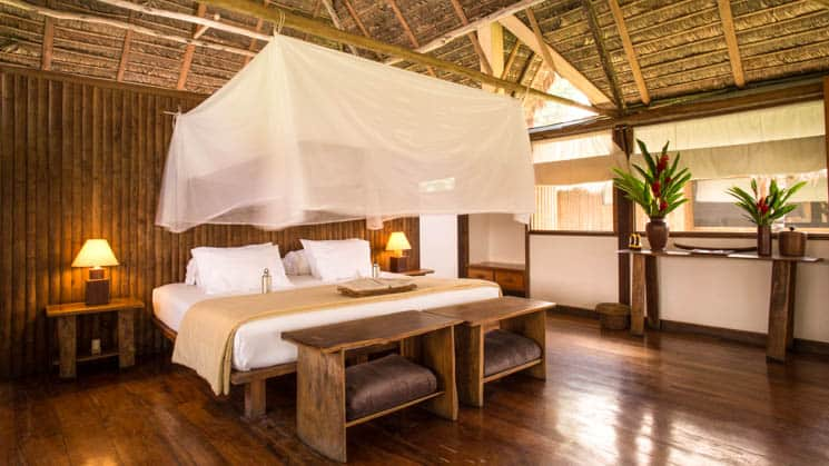 A king bed with a mosquito net, reading lights, open windows at the Tambopata Suite at Inkaterra Reserva Amazonica, an eco-luxury lodge in Peru.