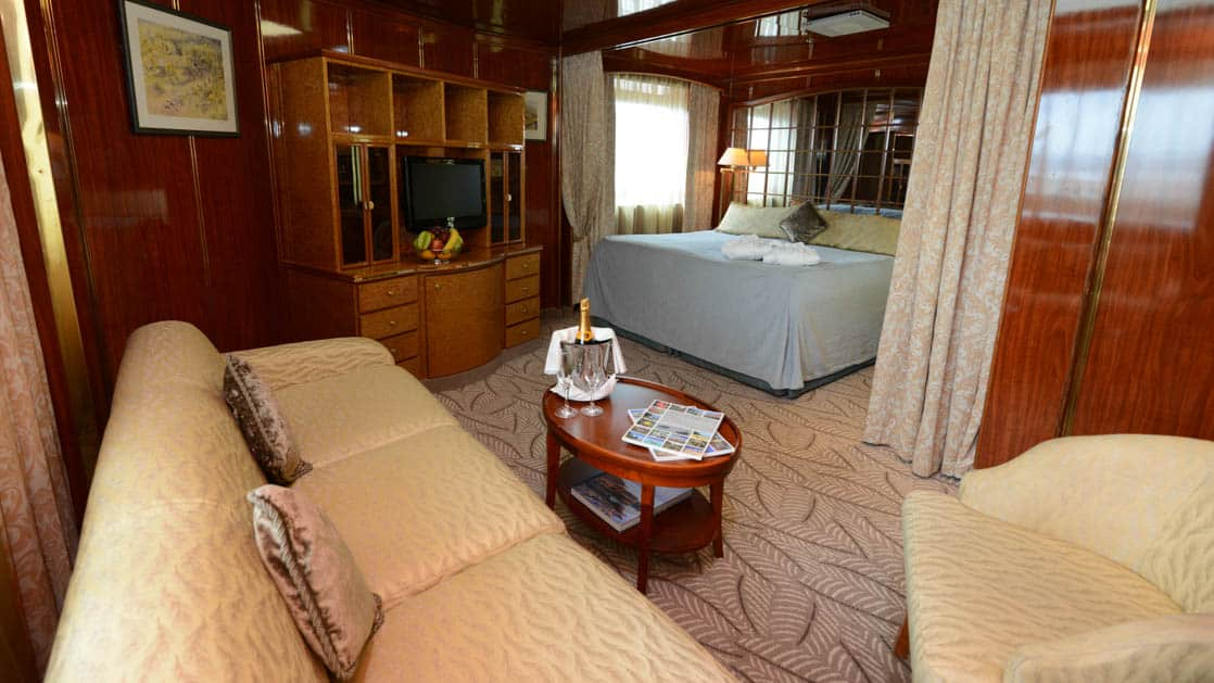 Island Sky Deluxe suite with queen bed, living room with couch, chair and coffee table, sliding glass door and large window.