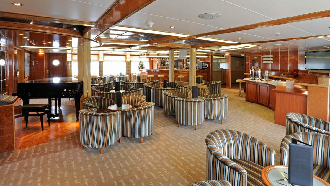 Lounge area with piano, chairs, cocktail tables, bar and service station aboard the Island Sky.