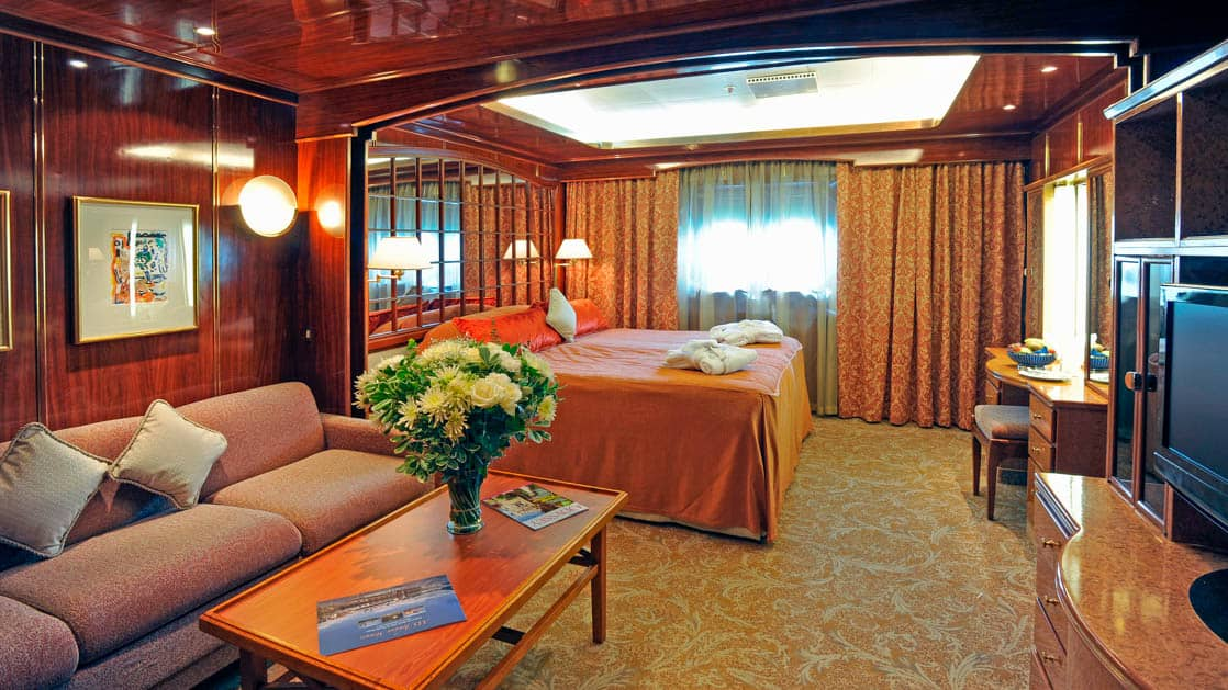 Island Sky Porthole suite with queen bed, porthole and living room with couch, chair and coffee table.