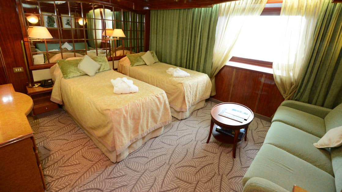 Island Sky Promenade suite with twin beds, large viewing window, couch, small coffee table and nightstands.