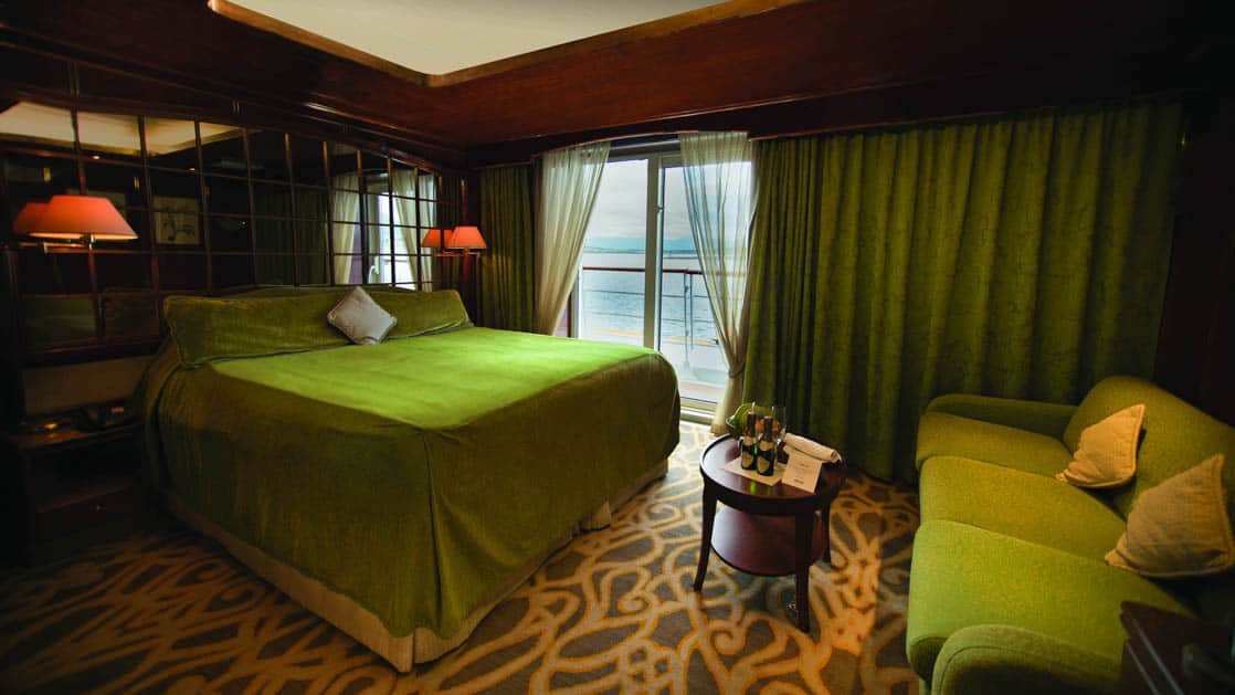 Island Sky Promenade suite with queen bed, couch, nightstands, reading lights and balcony.