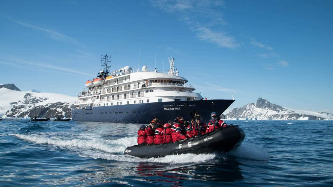 Island Sky anchored off the coast of Antarctica with a zodiac cruising with passengers.