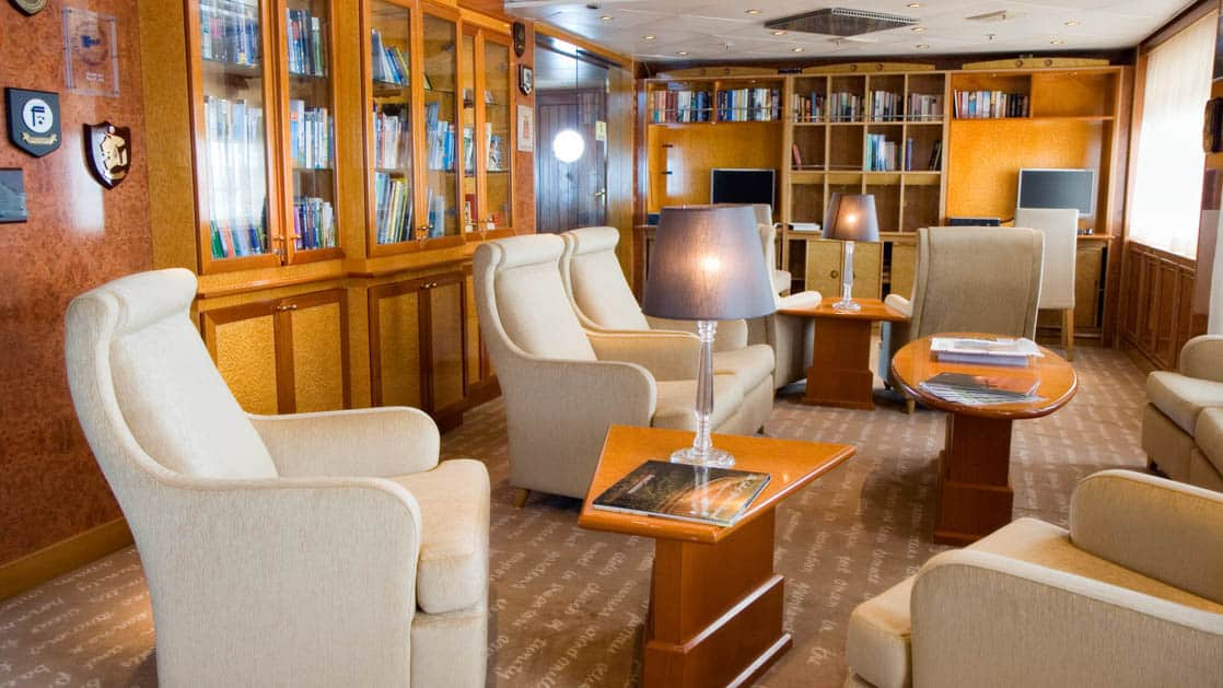 Island Sky library with large chairs, small tables, viewing windows and book shelf with assorted books.
