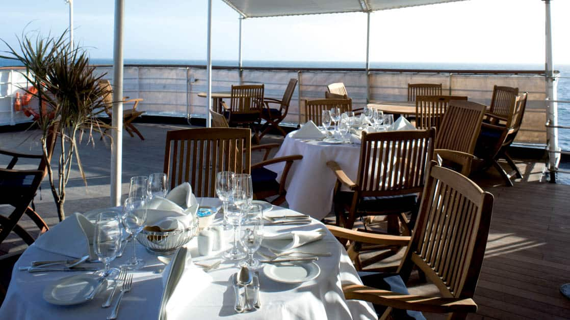 Outdoor dining on the deck with tables and chairs set up for a meal on the Island Sky.