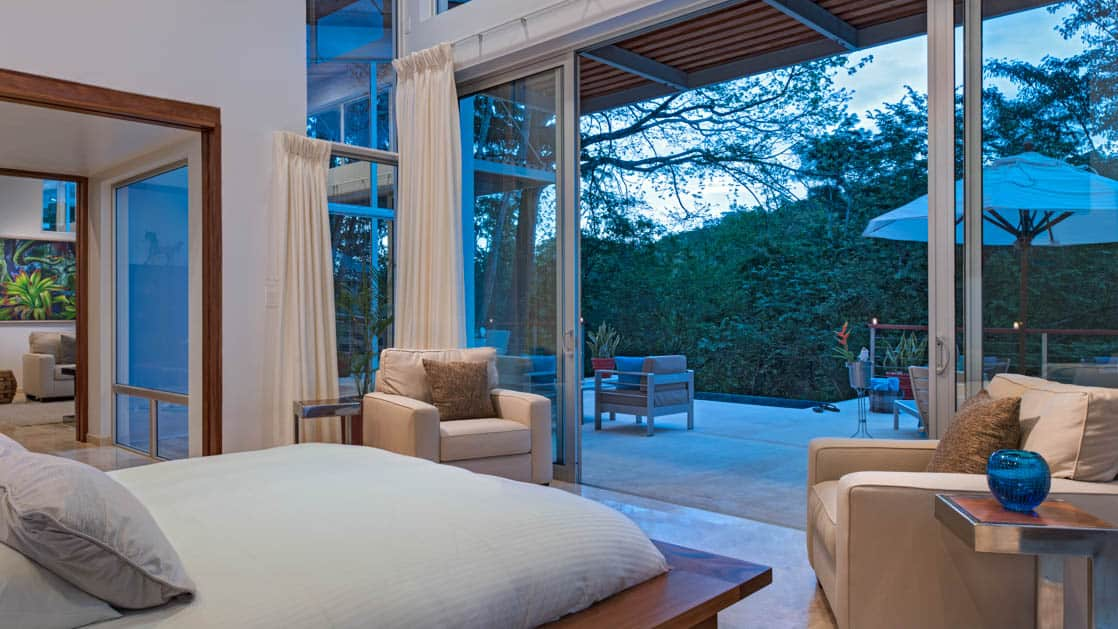 A large bedroom awash in natural light features large patio doors opening to an expansive outdoor living area with shaded lounge chairs and jungle views at Chaa Creek Jungle Lodge in Belize