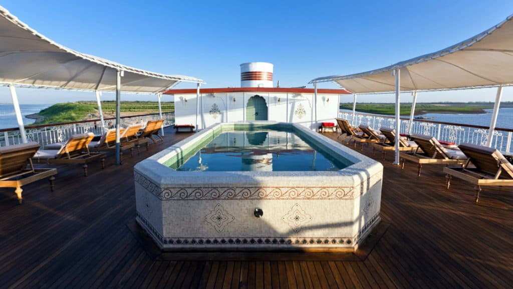 On the terrace deck is a small spa pool surrounded by deck chairs.