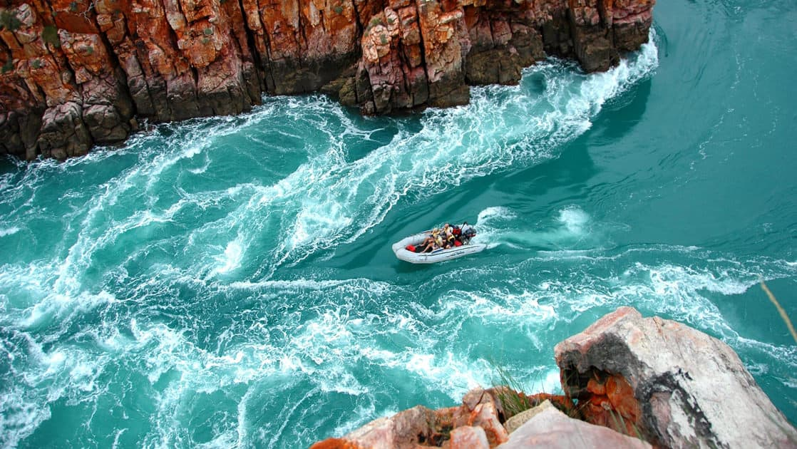 a zodiac skiff takes adventure travelers through a turquoise horizontal waterfall with cliffs on either side on the Kimberley Cruising to the Australian Outback trip