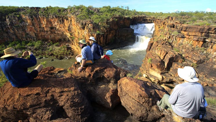 travelers relax atop sheer rocks on mitchell falls in the kimberley australia on a sunny day