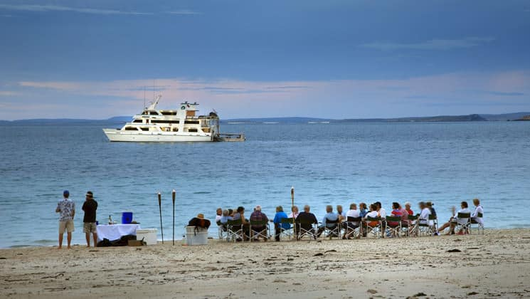 travelers relax on an australian beach in the evening with a small ship sitting on turquoise water and pink clouds are in the distance