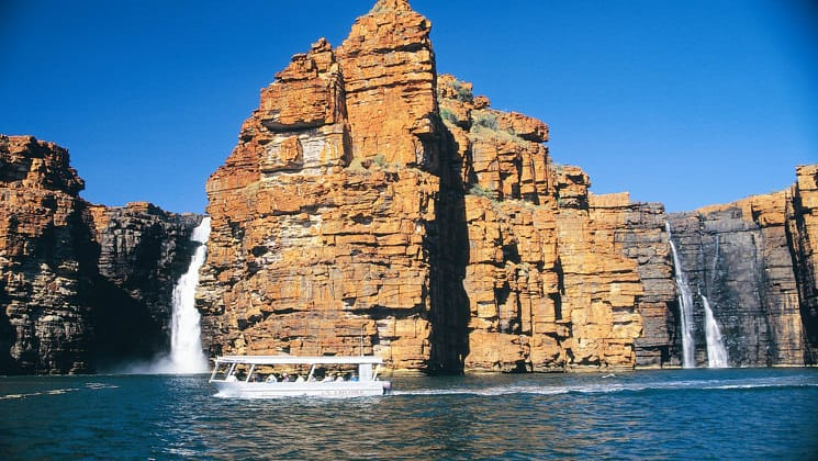 a small ship with adventure travelers in it cruises between several waterfalls coming out of sheer cliffs on the Kimberley - Cruising to the Australian Outback trip