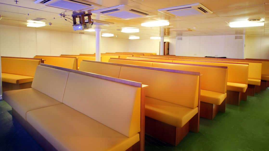 a lecture room with rows of pews aboard the ortelius small ship