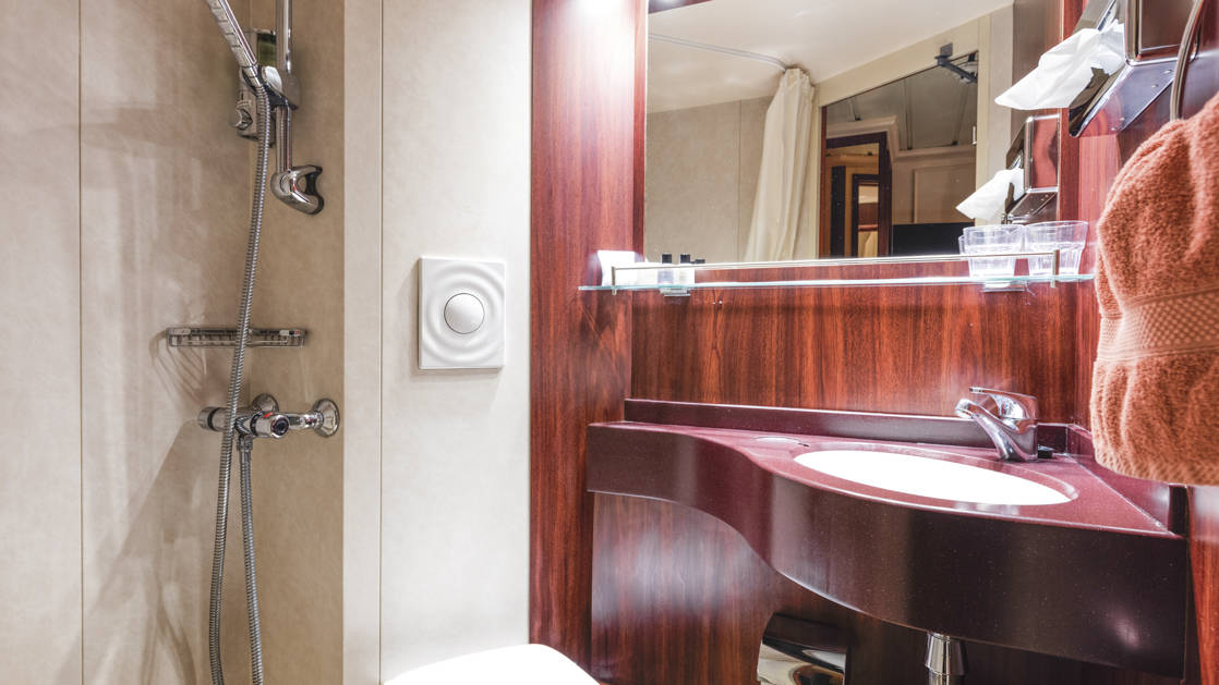 Lord of the Glens stateroom bathroom with shower, vanity, toilet and storage.