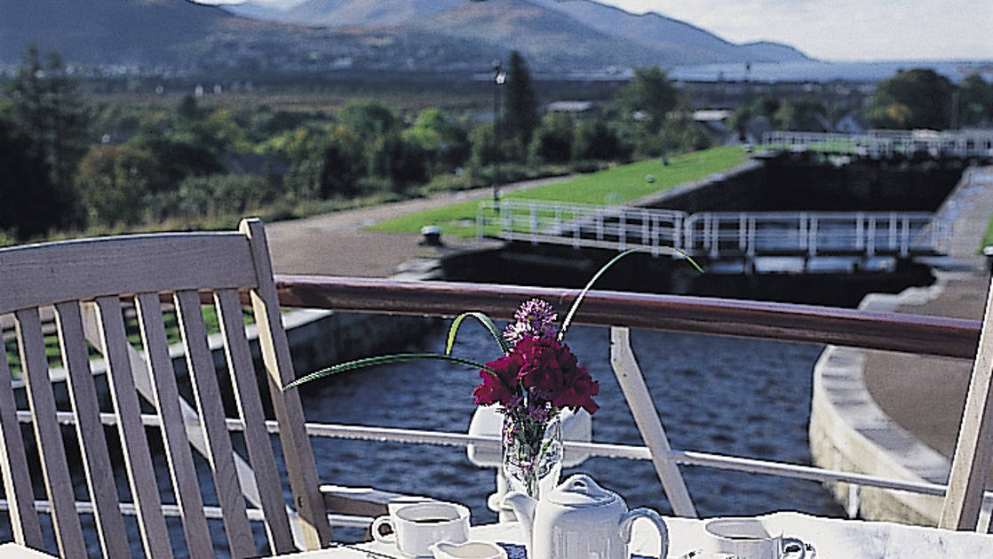 Lord of the Glens deck with a table and chair set up for tea with the locks behind the small ship cruise in Scotland.