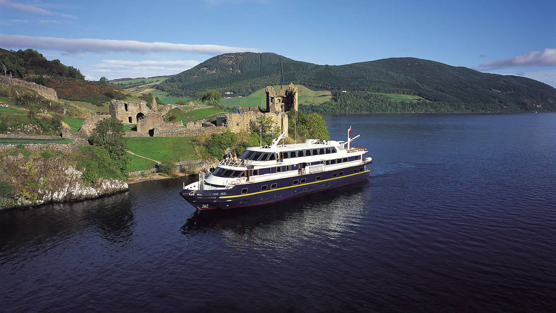 Small ship Lord of the Glens cruising past the Urquhart Castle in the Loch Ness highlands of Scotland