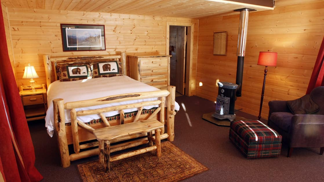 The interior of a rustic cabin with a full bed, wood-crafted furniture, reading lamps, a wood stove, and a private bathroom at Winterlake Lodge, an Alaska resort recognized by National Geographic for its wilderness experience