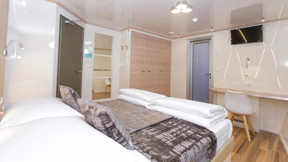 Maritimo stateroom with double bed, bathroom, closet, desk and seating.
