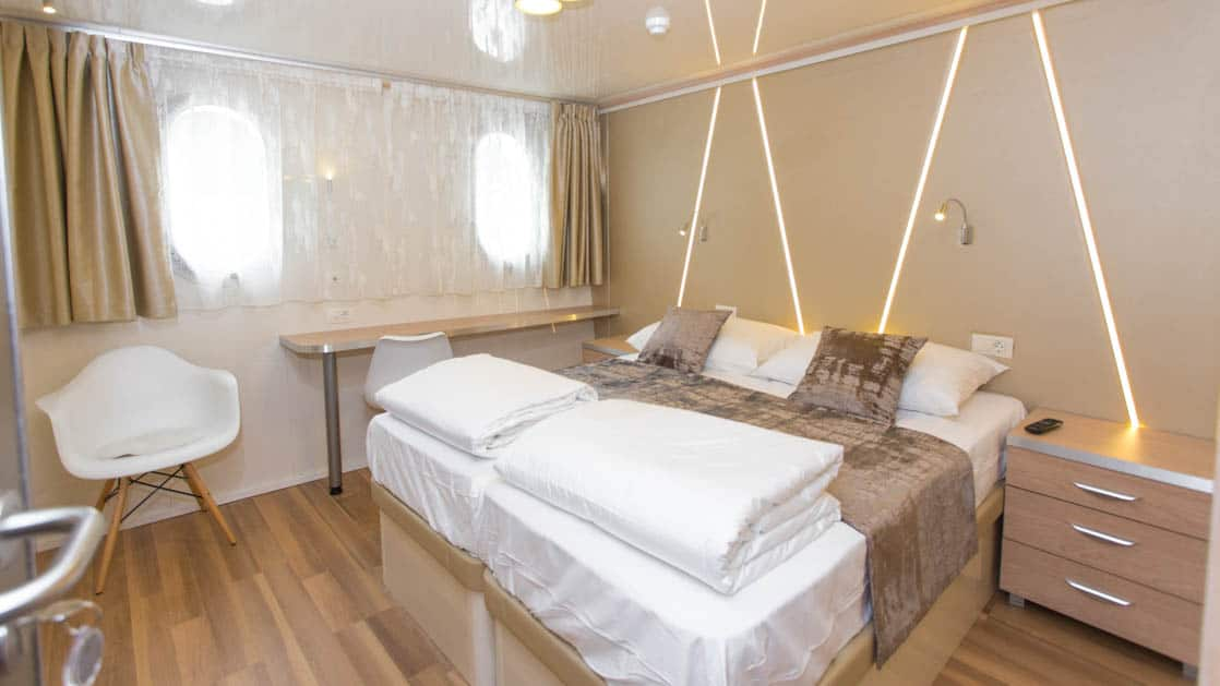 Maritimo Main Deck cabin with double bed, 2 windows, desk, seating, nightstand and reading light.