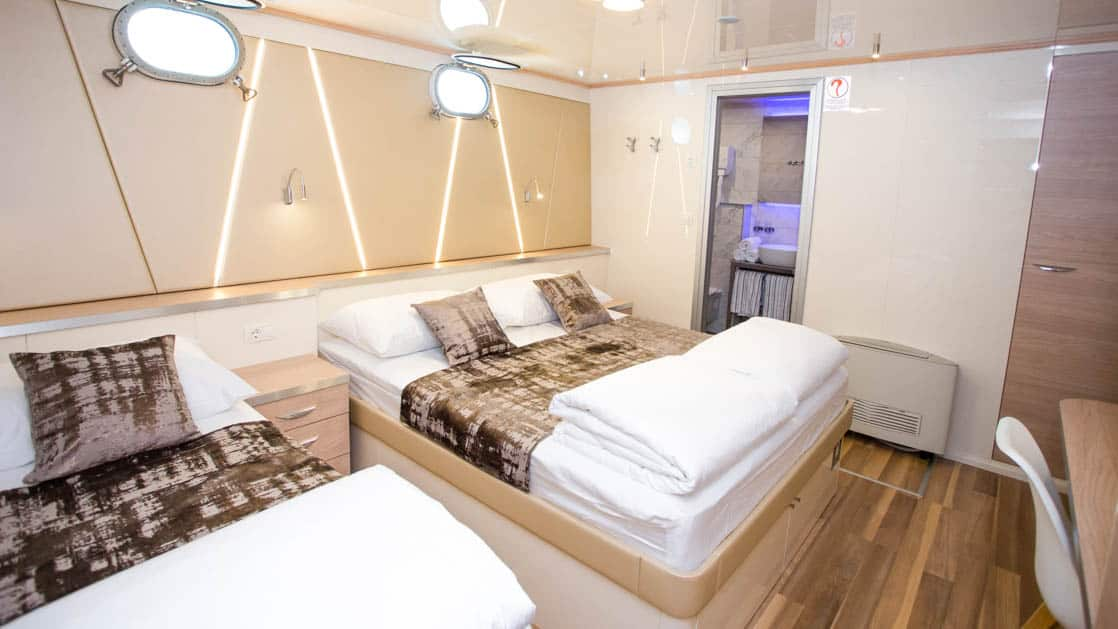 Maritimo lower deck stateroom with 2 double beds, 2 portholes, bathroom, desk and chair.