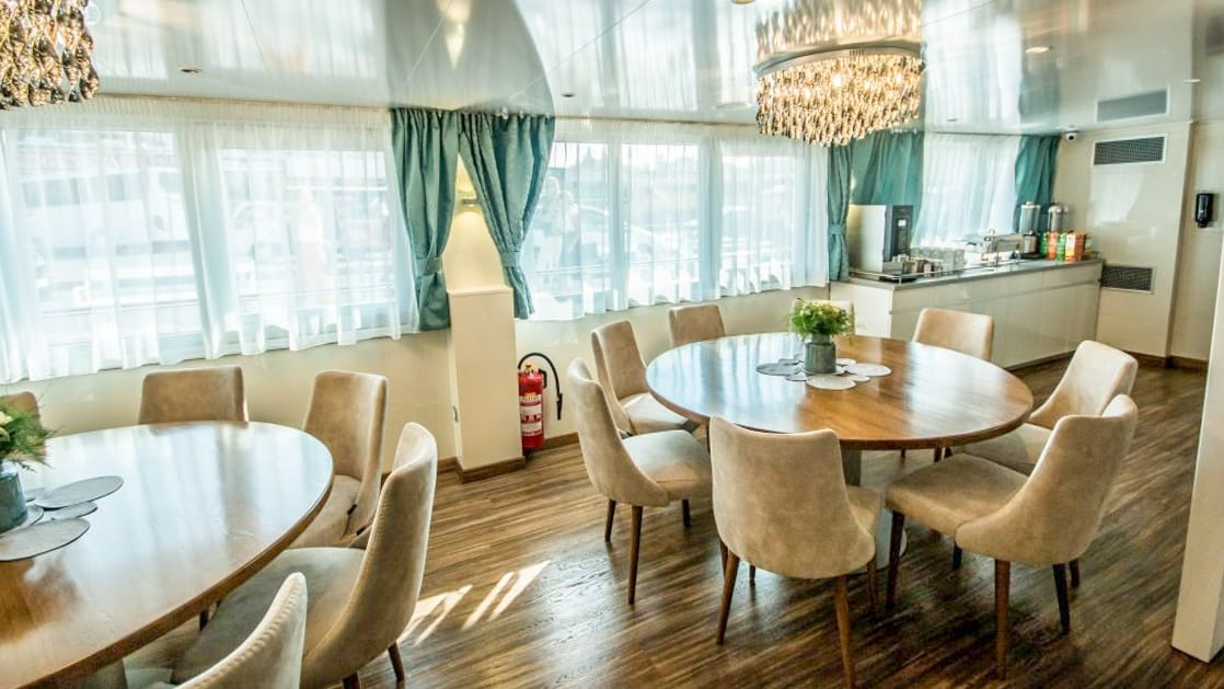 Markan Dining room with round tables, chairs, large windows and service station.